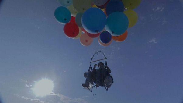 Accroché à des ballons gonflés à l'hélium