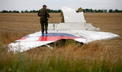 An armed pro-Russian separatist stands on part of the wreckage of MH17 three days after it was brought down in July 2014.