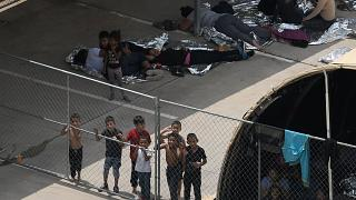 Image: Migrants are seen outside the U.S. Border Patrol McAllen Station in