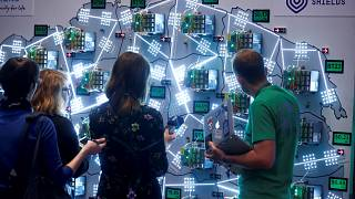 Image: People look at visualizations at a cyber defense exercise organize b