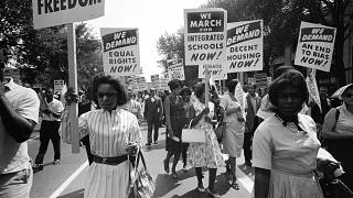Image: Demonstrators carry signs calling for equal rights and integrated sc
