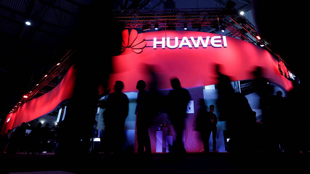 Image: Visitors walk past the Huawei booth at the Mobile World Congress in