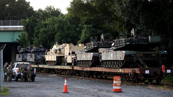 Image: M1A1 Abrams tanks and other military vehicles sit on rail cars in Wa
