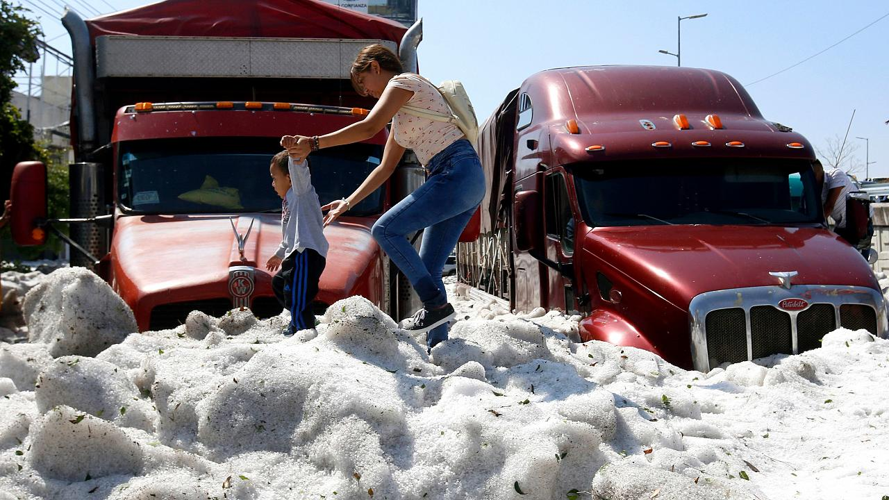 Image: A woman and child walk on a pile of hail in Guadalajara, Mexico, on