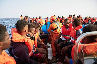 The German migrant rescue charity NGO Sea-Eye helps people to get off an overloaded rubber boat spotted in international waters off the Libyan coast.
