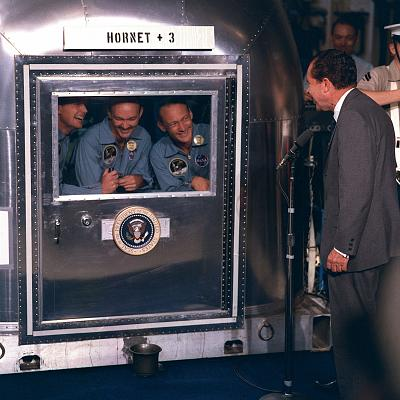 President Nixon welcomes the Apollo 11 astronauts who are confined in a quarantine facility aboard the USS Hornet.