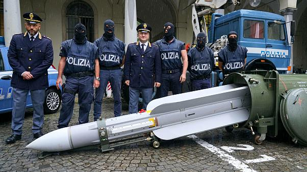 Image: Police stand with a missile seized at an airport hangar near Pavia a