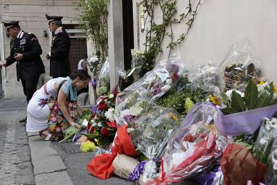 A woman leaves flowers in front of the Carabinieri station where Mario Cerciello Rega was based in Rome on Saturday.