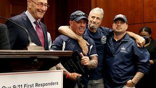 Image: Jon Stewart hugs 9/11 first responders with Sen. Chuck Schumer, D-NY
