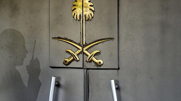 The shadow of a security member of the consulate is seen on the door of the