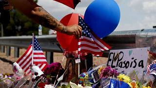 Image: A man places an American flag at a makeshift memorial near the site