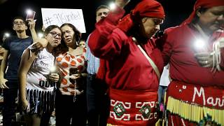Image: People embrace at a vigil for victims of a mass shooting that left 2