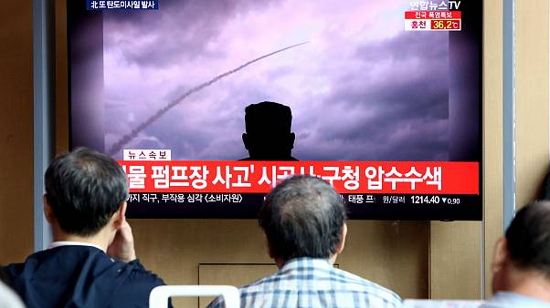 Image: People watch a TV showing a file image of a North Korea's missile la