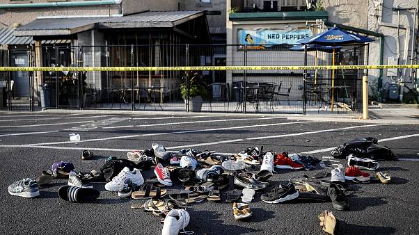 Image: A pile of shoes outside the scene of a mass shooting at Ned Peppers