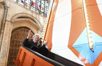 The Very Reverend Jane Hedges slides down the helter skelter inside Norwich Cathedral.