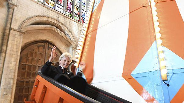 Image: The Very Reverend Jane Hedges slides down the helter skelter inside