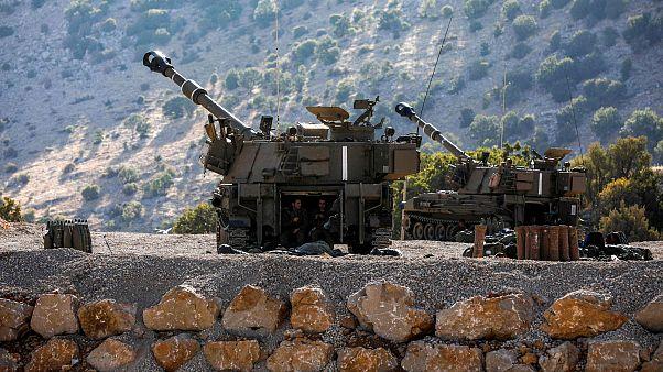 Image: Israeli soldiers sit inside a self-propelled artillery gun near the