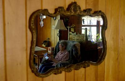 Audrey Buchanan, 88, is reflected in a mirror while she plays Animal Crossing on her pink Nintendo 3DS XL in the living room of her home in Berlin, Pa., on  Aug. 24, 2019.