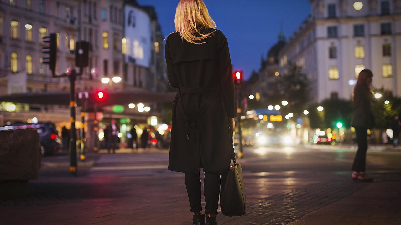 Rear view of woman walking on city street at night