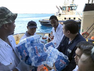 Crew of the Celebrity Equinox prepares pallets of bottled water for distribution in Freeport, Bahamas, on Sept. 5, 2019