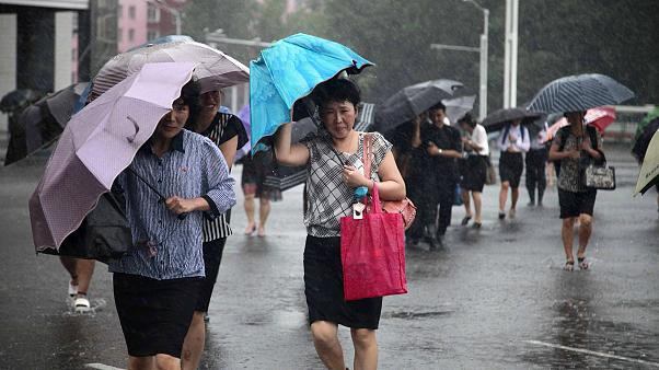 Image: Pedestrians shield themselves from wind and rain from Typhoon Lingli