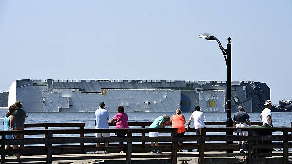 People look at a capsized cargo ship off the St. Simons Island Pier on Sept