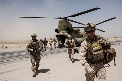 U.S. service members walk off a helicopter on the runway at Camp Bost in Helmand Province, Afghanistan on Sept. 11, 2017.