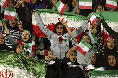 "Iranian women cheer as they wave their country\'s flag after authorities in a rare move allowed a select group of women into Azadi stadium to watch a friendly soccer match between Iran and Bolivia, in Tehran, Iran on Oct. 16, 2018.  Sahar Khodayari, an Iranian female soccer fan died after setting herself on fire outside a court after learning she may have to serve a six-month sentence for trying to enter a soccer stadium where women are banned, a semi-official news agency reported Tuesday, Sept. 10, 2019. The 30-year-old was known as the ""Blue Girl"" on social media for the colors of her favorite Iranian soccer team, Esteghlal."