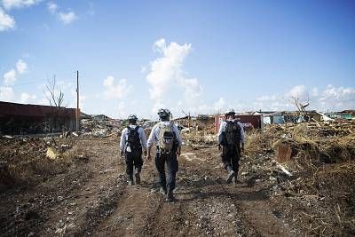 Three search and rescue workers scan the neighborhood of the Mudd in Marsh Harbour, Abaco Island, Bahamas, for bodies of victims in the rubble.