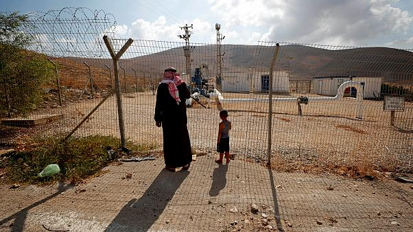 Image: Palestinians stand at a fence separating the Jordan Valley and the I