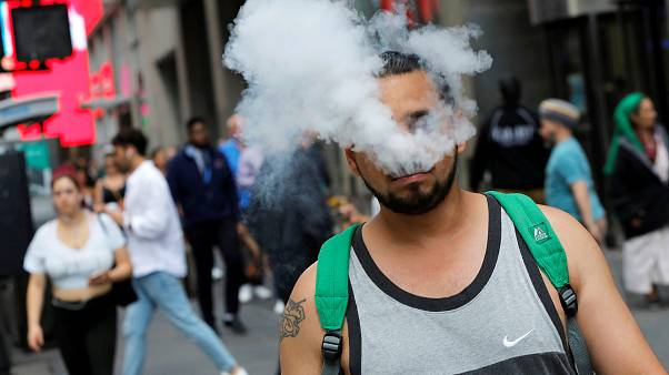 Image: A man uses a vape as he walks on Broadway in New York City