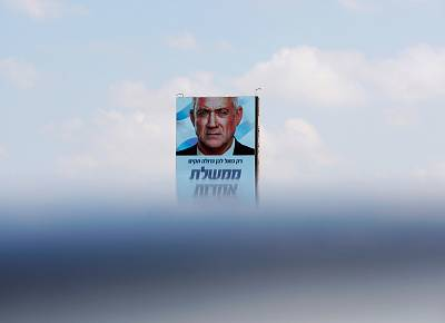"""Benny Gantz, leader of Blue and White party in an election campaign banner that reads, """"Only a big Blue and White party will establish a unity government"""" in Tel Aviv on Sept. 9, 2019."""
