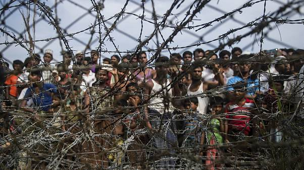 Image: Rohingya refugees gathering behind a barbed-wire fence in a temporar