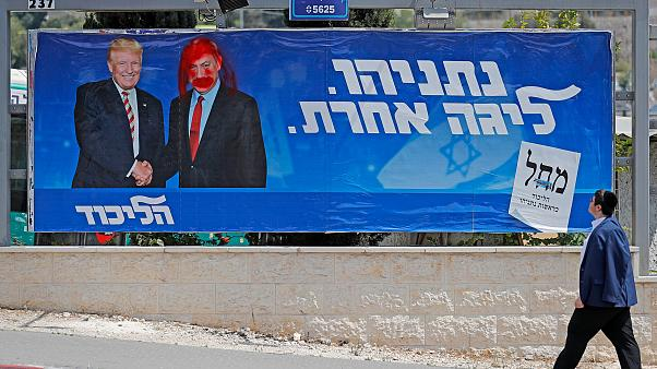 Image: An Israeli man looks at a defaced election billboard for the Likud p