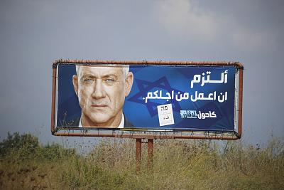 "An election campaign billboard shows the Blue and White party leader Benny Gantz, in the Arab town of Baqa al-Gharbiyye, northern Israel. The Arab writing says, "" I commit to work for you."""
