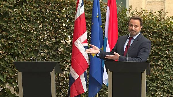 Image: Luxembourg's Prime Minister Xavier Bettel gestures to an empty podiu