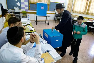 A child accompanies an ultra-Orthodox Jewish man as he casts his ballot at a voting station in the city of Bnei Brak during the Israeli parliamentary election on Sept. 17, 2019.