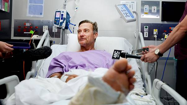 Image: Neil Parker speaks to reporters from his hospital bed while recoveri