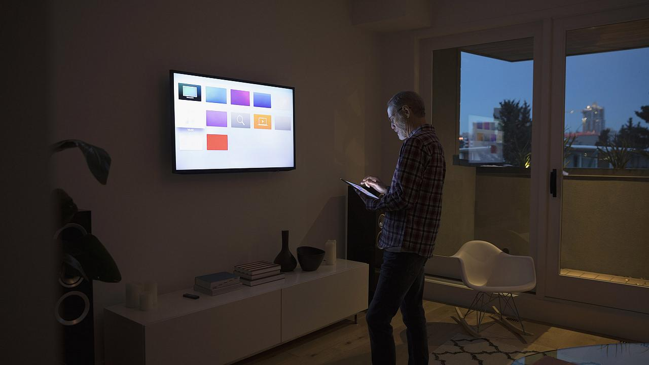 Image: A man using smart TV apps via a digital tablet.
