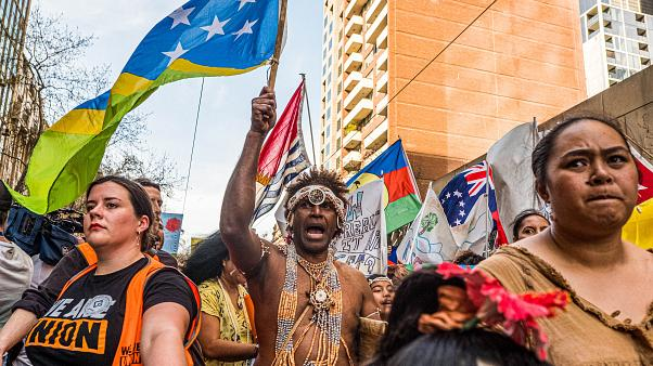 Image: A man wearing the traditional dress of the Solomon Islands march on