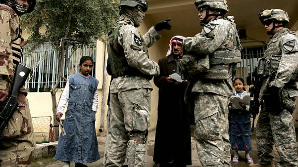 Image: An Iraqi man answers questions from U.S. soldiers with the help of a