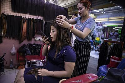 A hairdresser works on a customer at the Orussey shopping complex in Phnom Penh.