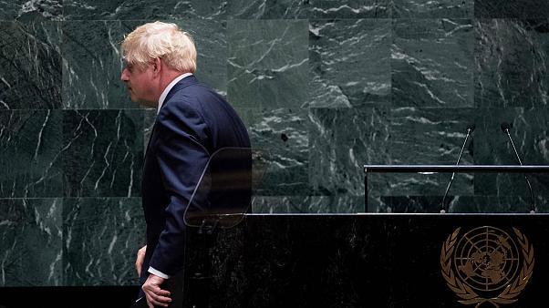 Image: British Prime Minister Boris Johnson walks off after speaking at the