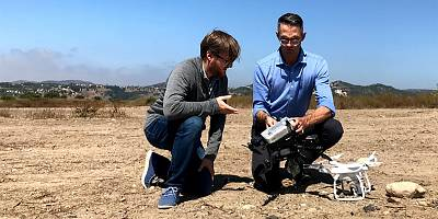 """Anduril co-founder and CEO Brian Schimpf shows NBC\'s Jacob Ward the company\'s new """"Interceptor"""" drone outside its test facility near Irvine, California."""