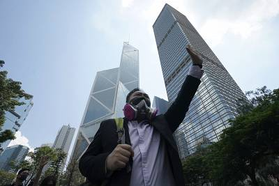 A protester wears a gas mask and holds up his hand to represent the five demands in Hong Kong on Friday.