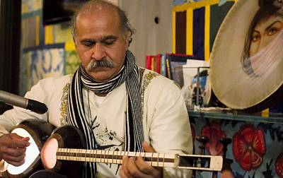 Karim Alishahi plays his setar. While his wife and daughter usually take care of the food and storytelling component, he uses his traditional music to create a connection with Italian guests.