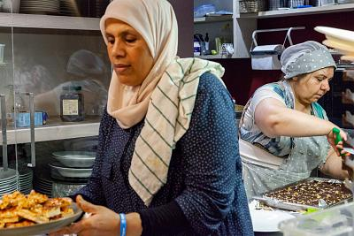Kholoud Marei, left, and Maryam Khoshluie prepare Middle Eastern sweets to go with tea and other hot drinks during one of the community\'s events held at Orient Experience.