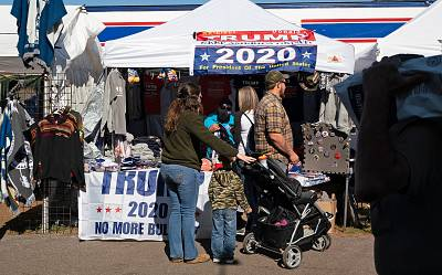 Fairgoers walk past a vendor selling paraphernalia supporting President Donald Trump at the Fryeburg Fair in Maine on Saturday.