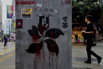 People walk near graffiti on a pillar which shows Hong Kong Special Administrative Region flag pattern drawn in  black and red in Hong Kong, Monday, Oct. 7, 2019.