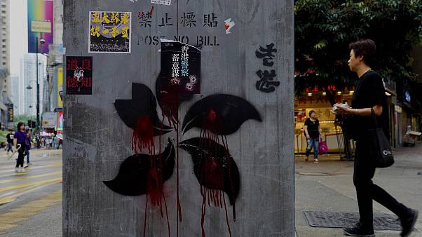 Image: People walk near graffiti on a pillar which shows Hong Kong Special